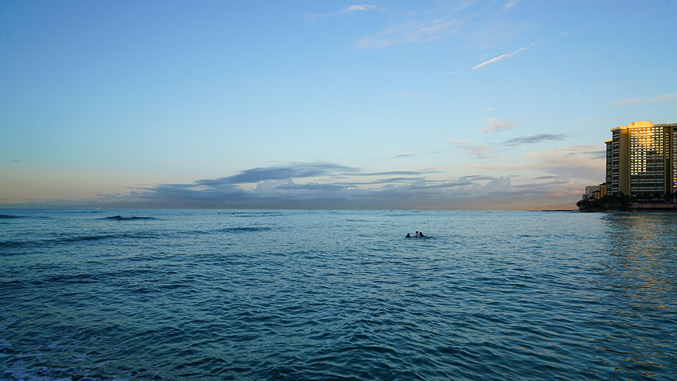Looking over the water at sunset from Waikiki Beach.
