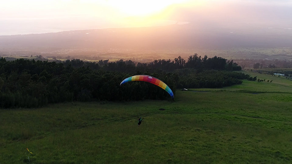 A smiling woman in the air paragliding.