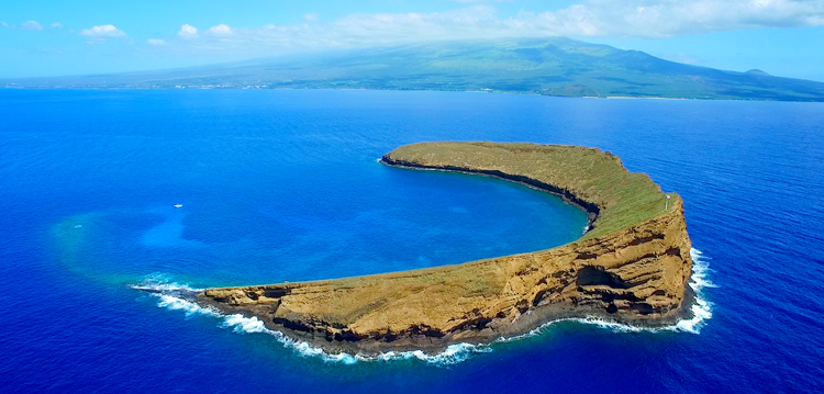 molokini island on a blue sky and ocean day with maui in the background