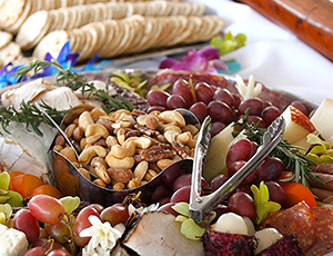 Food spread of grapes, nuts, crackers, and cheese.